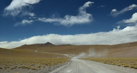 Safari car moving fast in the dust, crossing the bolivian andes, highlands