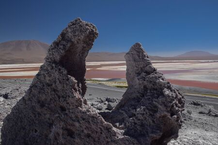 geometric special stone in front of red lagoon in the bolivian highlands.