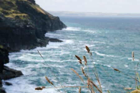Wild scene with sea, stones, rocks coastline and grass in front. Picture taken on remaining tintagel castle, king arthur's castle un cornwall, UK, England