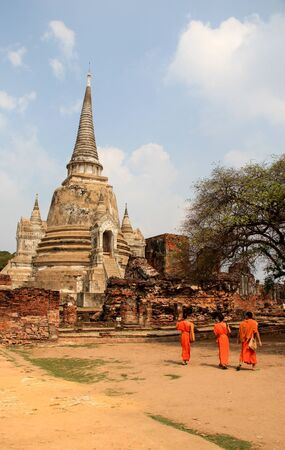 Young monk novices walking in front of an ancient buddhistic ruin, Thailand
