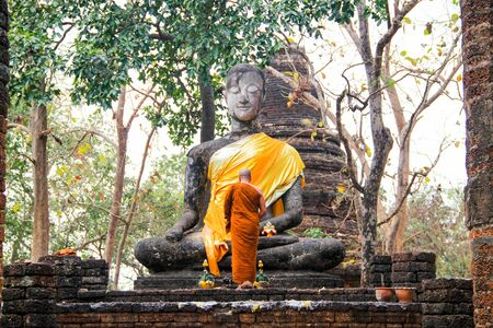 A buddhistic monk in orange dress is praying in front af an ancient statue, Sukothai, Thailand