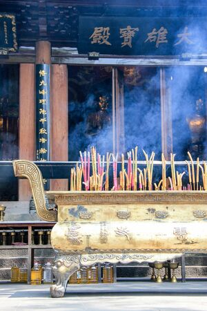 Purple and yellow incense sticks burning at an altaran in front of a temple