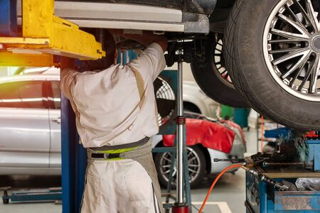 An auto mechanic standing under the car that is on lifting platform, car repair