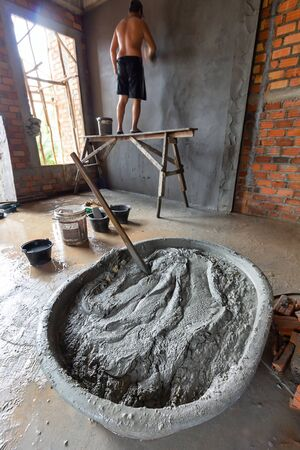 A worker mixing cement mortar plaster for interior walls, Mixing mortar.