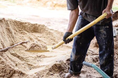 Un lavoratore usa la pala per riempire la sabbia nella carriola per la costruzione di una nuova casa. Strumenti di costruzione.