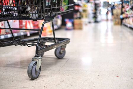 Shopping cart focusing on its wheel in department store, supermarket interior.