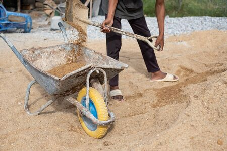 A worker use the shovel to fill the sand into the wheelborrow for construction of new house. Construction tools