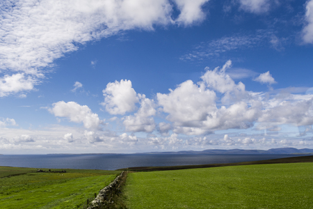 Orkney islands landscape, green grass, blue sky