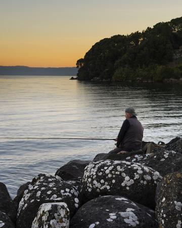 Fisherman on the lake at sunrise in Bolsena