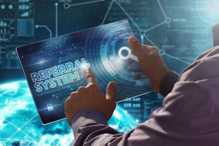 Internet. Business. Technology concept. Businessman presses a button Referral System on the virtual screen tablet future date.