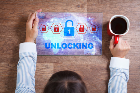 unlocking: Business, Technology, Internet and network concept. Young business woman with a cup of coffee, working on the tablet of the future, select on the virtual display:  Unlocking
