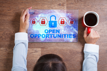 decode: Business, Technology, Internet and network concept. Young business woman with a cup of coffee, working on the tablet of the future, select on the virtual display:  Open opportunities