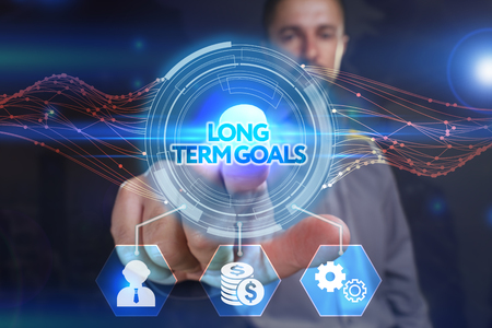 long term: Business, Technology, Internet and network concept. Young businessman, select on the virtual display: long term goals