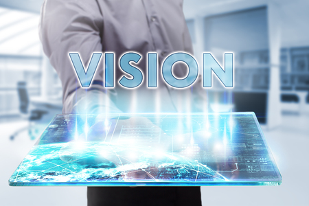 domain: Business, Technology, Internet and network concept. Young businessman working on a tablet of the future, he sees the inscription: vision Stock Photo