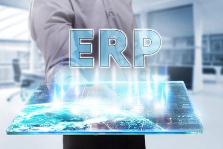 Business, Technology, Internet and network concept. Young businessman working on a tablet of the future, he sees the inscription: ERP