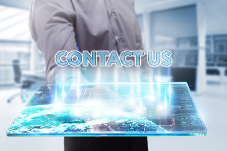 Business, Technology, Internet and network concept. Young businessman working on a tablet of the future, he sees the inscription: contact us