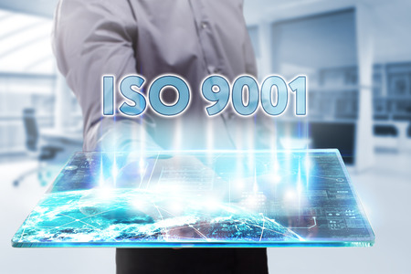 Business, Technology, Internet and network concept. Young businessman working on a tablet of the future, he sees the inscription: ISO 9001