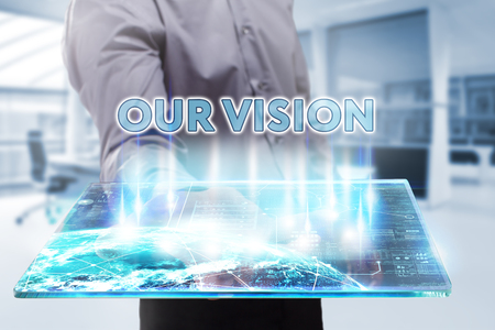 our vision: Business, Technology, Internet and network concept. Young businessman working on a tablet of the future, he sees the inscription: our vision