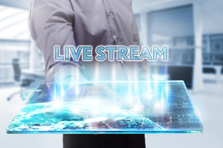 Business, Technology, Internet and network concept. Young businessman working on a tablet of the future, he sees the inscription: live stream