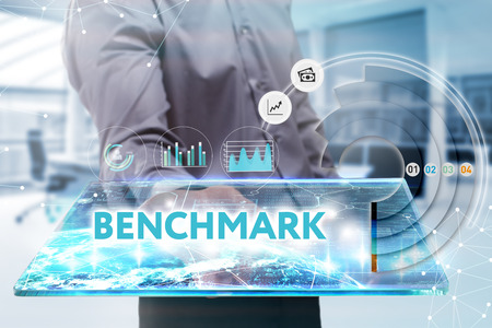 Business, Technology, Internet and network concept. Young businessman working on a tablet of the future, he sees the inscription: benchmark