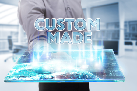 custom made: Business, Technology, Internet and network concept. Young businessman working on a tablet of the future, he sees the inscription: custom made