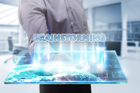 domain: Business, Technology, Internet and network concept. Young businessman working on a tablet of the future, he sees the inscription: brainstorming Stock Photo