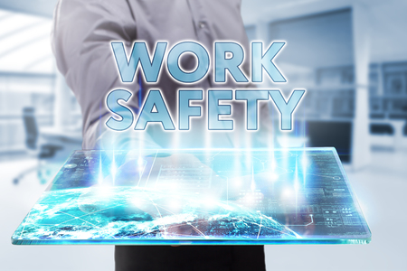 Business, Technology, Internet and network concept. Young businessman working on a tablet of the future, he sees the inscription: work safety Stock Photo