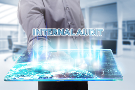 internal audit: Business, Technology, Internet and network concept. Young businessman working on a tablet of the future, he sees the inscription: internal audit