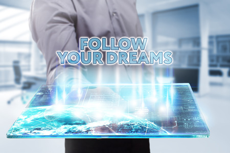Business, Technology, Internet and network concept. Young businessman working on a tablet of the future, he sees the inscription: follow your dreams