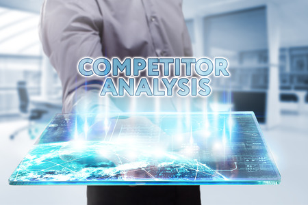 competitor: Business, Technology, Internet and network concept. Young businessman working on a tablet of the future, he sees the inscription: competitor analysis