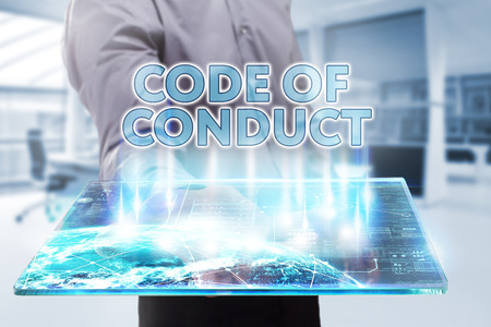 Business, Technology, Internet and network concept. Young businessman working on a tablet of the future, he sees the inscription: code of conduct