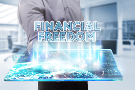 financial freedom: Business, Technology, Internet and network concept. Young businessman working on a tablet of the future, he sees the inscription: financial freedom Stock Photo