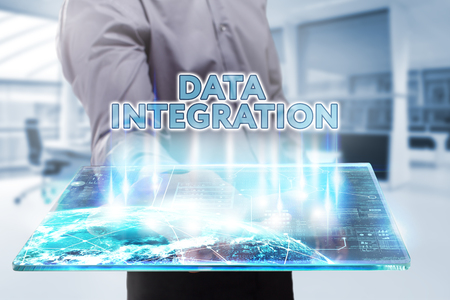 Business, Technology, Internet and network concept. Young businessman working on a tablet of the future, he sees the inscription: data integration Stock Photo