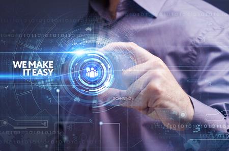 ビジネス、技術、インターネット、ネットワークのコンセプトです。未来の仮想画面に取り組んでいる青年実業家と碑文を見ている: それを簡単
