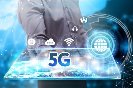 ビジネス、技術、インターネット、ネットワークのコンセプトです。若いビジネスマン、将来のタブレットに取り組んで彼は碑文を見ている: 5 G