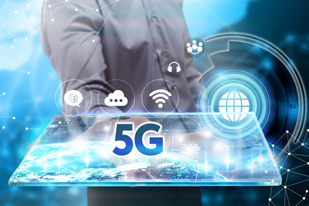 Business, Technology, Internet and network concept. Young businessman working on a tablet of the future, he sees the inscription: 5G