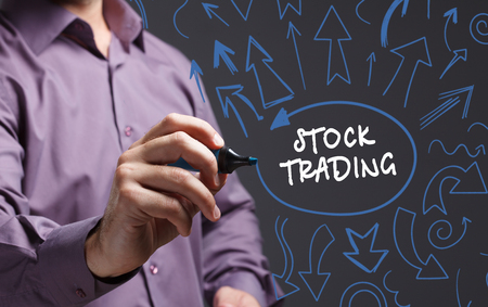 trading questions: Technology, internet, business and marketing. Young business man writing word: stock trading