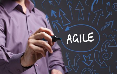 agile: Technology, internet, business and marketing. Young business man writing word: agile