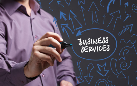 business services: Technology, internet, business and marketing. Young business man writing word: business services