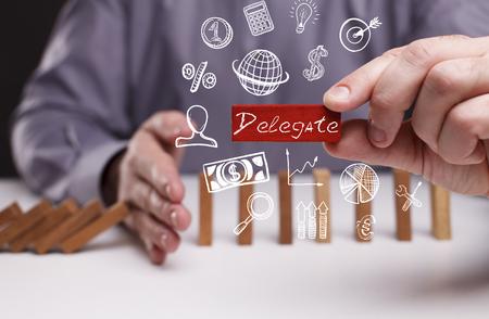 delegar: Negocio, Tecnología, Internet y el concepto de red. Joven hombre de negocios muestra la palabra: Delegado