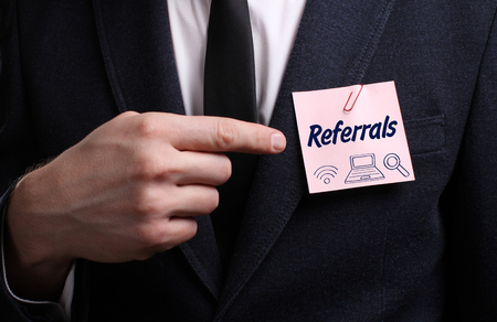 referidos: Business, Technology, Internet and network concept. Young businessman shows the word: Referrals