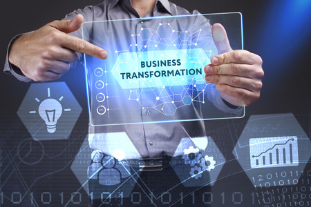 Business, Technology, Internet and network concept. Young businessman showing a word in a virtual tablet of the future: Business transformation Archivio Fotografico