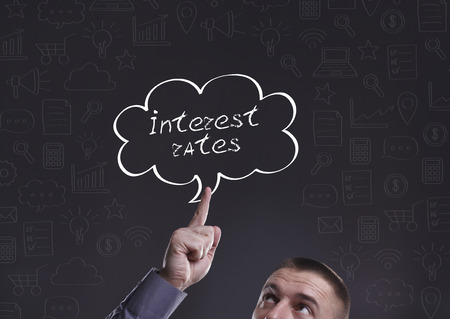 interest rates: Business, Technology, Internet and marketing. Young businessman thinking about: Interest rates