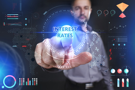interest rates: Business, Technology, Internet and network concept. Young businessman showing a word in a virtual tablet of the future: Interest rates