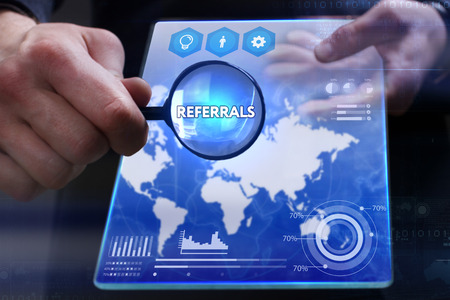 referidos: Business, Technology, Internet and network concept. Young businessman showing a word in a virtual tablet of the future: Referrals Foto de archivo