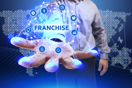 Business, Technology, Internet and network concept. Young businessman shows the word on the virtual display of the future: Franchise