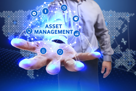 Business, Technology, Internet and network concept. Young businessman shows the word on the virtual display of the future: Asset management Archivio Fotografico