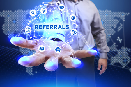 referidos: Business, Technology, Internet and network concept. Young businessman shows the word on the virtual display of the future: Referrals