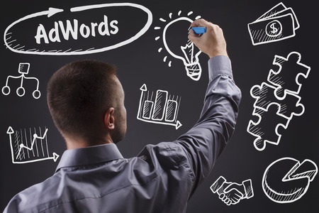 adwords: Technology, internet, business and marketing. Young business man writing word: AdWords Stock Photo