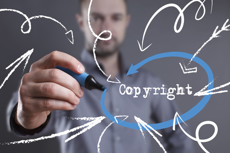 Technology, internet, business and marketing. Young business man writing word: Copyright
